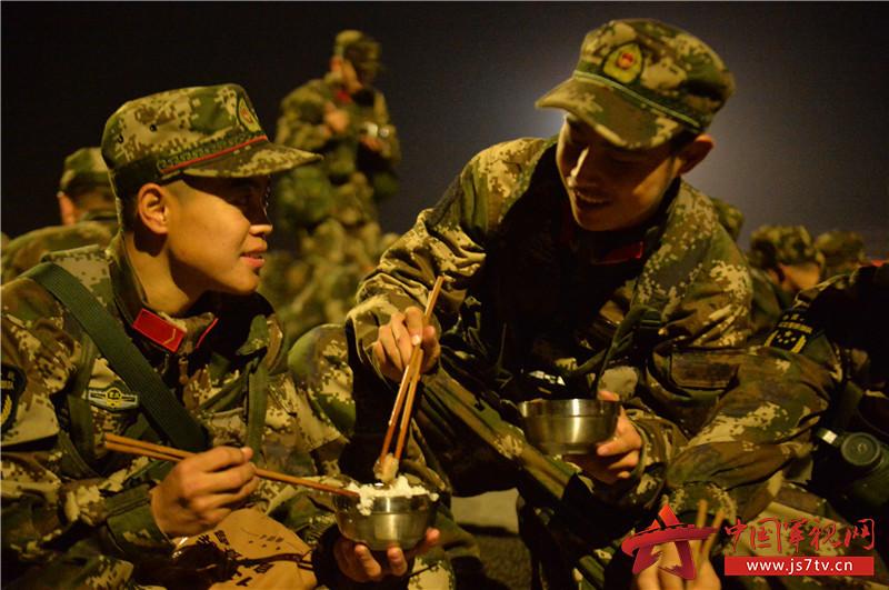 图为12月7日,武警重庆总队新兵团组织野外综合拉练,国防生学员为新兵夹菜。 (石路摄)