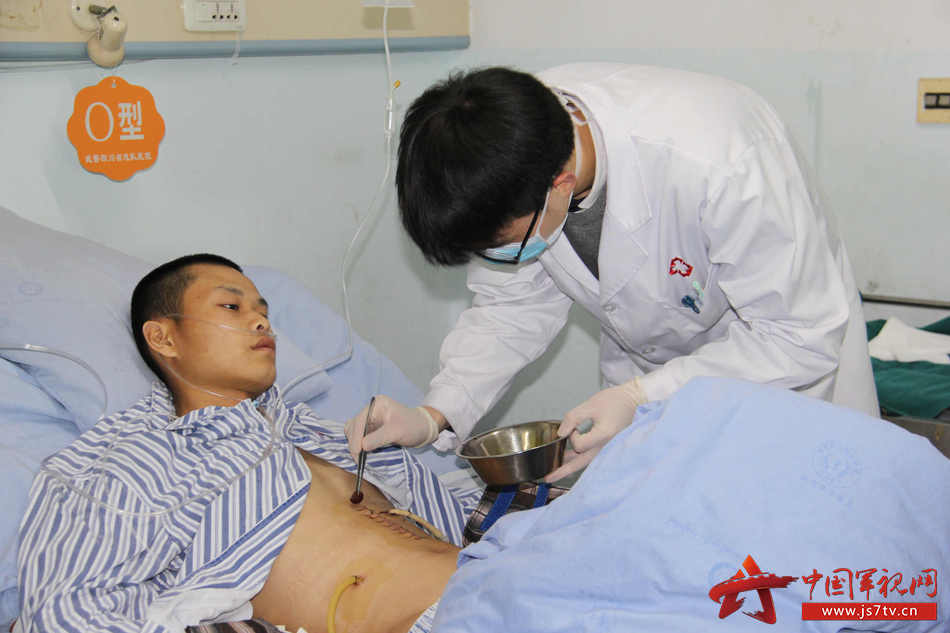 02护士正在给袁成涛更换药品。李华时摄