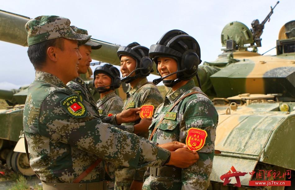 """舒海峰为连队即将参加比武的战士佩戴""""党员先锋队""""臂章。"""