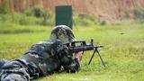 图为特战队员在雨中进行轻机枪对集团目标射击