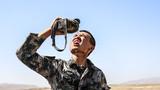 射击结束后,天气炎热,战士喝水场面。 王鹏飞  摄