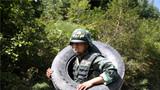 一名特战队员背轮胎抢占坡顶。