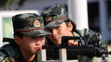 武警女兵班长唐霜(右)在教本班战士瞄枪训练。