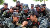 武警女兵余蕾(左)在训练休息间隙和班长唐霜(右)玩起了扳手腕游戏。