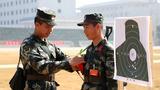 2018年11月29日,武警新兵蔡兆鵬(右)在打出五十環好成績后,指導員羅翔為他戴上紅花。