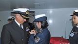 11月29日,中国海军和平方舟医院船女兵为登船参观的智利海军代表别上中国海军小徽章。江山摄