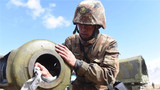 為保證射擊精度和安全,炮班戰士在射擊間隙擦拭火炮。潘濤 攝