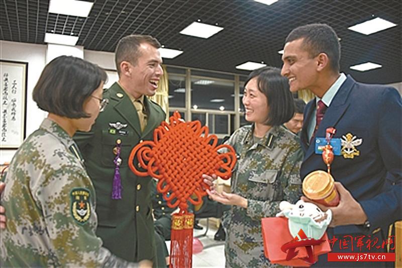 陆军工程大学学员在为外军学员介绍中国结(0)。