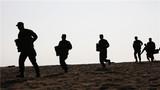 武警官兵抬着弹药箱在海滩全力奔袭。