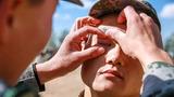 """官兵们积极踊跃参与第一届""""铁拳杯""""创破记录比武暨军事体育运动会,战士何祥福在比武时眼睛不小心进了沙子,卫生员正在为其进行处理。"""