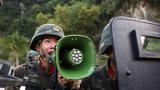 """一名特战队员对""""暴恐分子""""进行喊话,实施心理干预。"""