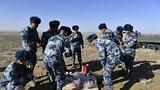 官兵们在戈壁滩上就着风沙吃着自带的午餐。