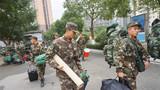 官兵争先上前为新战友们搬运行李。