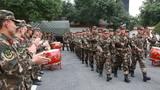 """支队官兵在道路旁迎接新战友""""回家""""。"""