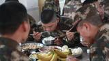 在饭堂里,炊事员为新战友们盛好了热腾腾的饭菜。