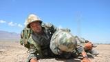 战场救护,卫生员在沙石地上侧姿搬运伤员。(薛宗炎 摄)