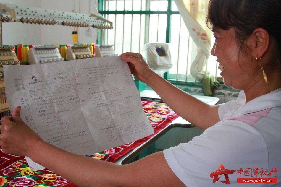 卫生员_图为杨幺妹拿着孩子100分的试卷情不自禁的笑起来