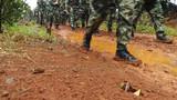 穿过泥泞的山路时,战士们的鞋上沾满了泥土。