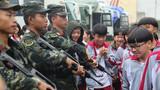 野营拉练期间,部队在训练区域的中学宿营。图为拉练部队在学校组织国防教育活动。