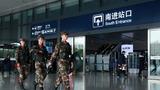 武警官兵正在火车东站进站口进行武装巡逻。