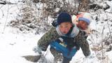 2018年2月2日,9岁半的吉觉吉竹背着1岁半的弟弟下山,前往四川省凉山彝族自治州越西县申果乡沙苦新村的外公家。新华社记者 田建川 摄