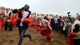 2018年10月20日,在陕西延安安塞区南沟进行的一场腰鼓演出结束后,一名外国游客与当地腰鼓手共同打起了腰鼓。新华社记者 刘潇 摄