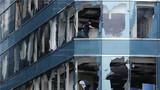 """2018年9月17日,在位于香港九龙半岛红磡海滨的一座写字楼中,工作人员在清理因台风""""山竹""""导致窗户破损的办公室。新华社发(王申 摄)"""