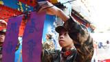 武警官兵将写好的春联挂起来,供现场群众挑选。
