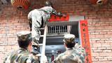 武警官兵为困难群众贴春联,将春节祝福送到家门口。
