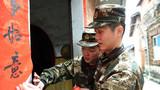 中队指导员带领官兵为困难群众贴春联。