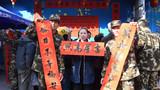 驻地群众拿到春联后开心地与武警官兵合影。