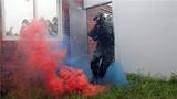捕歼战斗训练中,特战队员利用烟雾弹进行突击。
