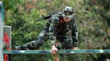 在四百米障碍项目中,参赛官兵正在通过高板障碍。