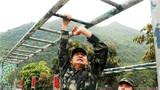 在四百米障碍项目中,参赛官兵正在通过悬梯障碍。