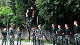 在器械竞赛项目中,参赛官兵正在完成单杠科目。