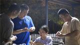 一位小姐姐耐心地教兵哥哥們包餃子。