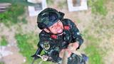 一名武警特战队员咬牙坚持进行抓绳训练