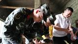 武警官兵与当地群众一起包粽子。