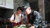 武警战士与阿姨一同包粽子。