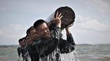 特战队员在海水中进行推举圆木训练。