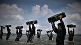 特战队员在海水中进行推举子弹箱训练。