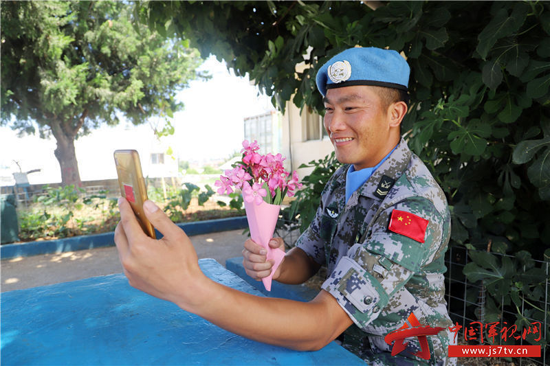 四级军士长杨金明在给妻女打视频电话时送上提前准备的野花--孙帅摄