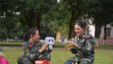 两名女兵正在交流花灯制作技巧