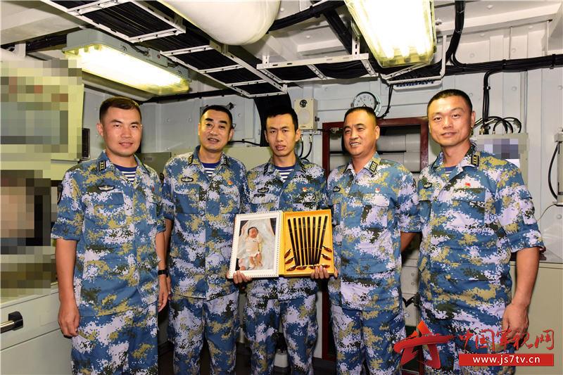 指挥员为徐广钊赠送护航宝宝相册和礼物。王冠彪摄影