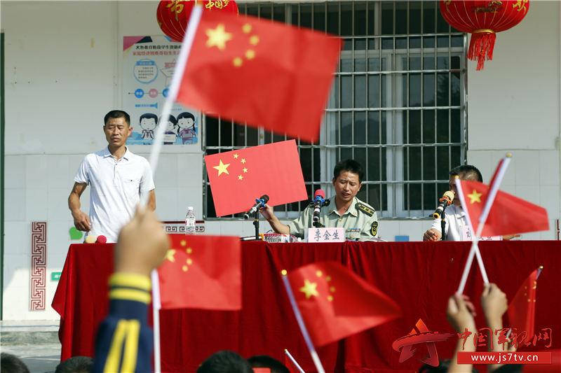03、讲述国旗图案意义时,学生们举起了手中的小国旗