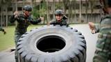 一名特战队员正在进行翻动重卡外轮胎训练。