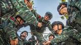 """  近日,武警广西总队玉林支队开展野外驻训。其间,特战队员们利用现有条件在训练间隙开展丰富多彩的互动游戏,让特战队员身心在紧张的训练中得到了有效放松,进一步增强了特战队员参训的积极性,让他们能够以更加昂扬的斗志全身心投入训练。图为""""穿越封锁线""""。"""