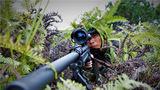 """捕歼战斗科目中,一名狙击手依托灌木丛隐蔽观察""""敌""""情。"""