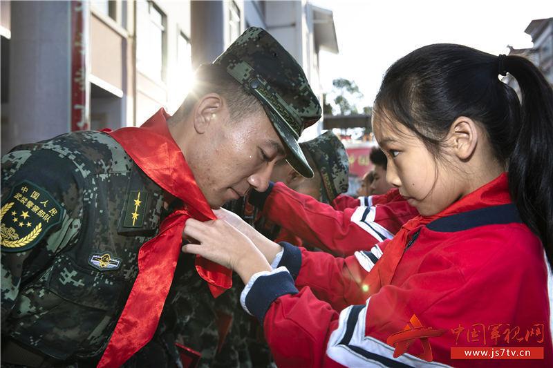 图一:小学生们为武警官兵佩戴红领巾