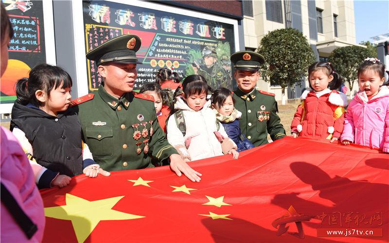 """图12:2019年12月27日,安徽合肥,在武警合肥支队""""军营开放日""""活动现场,武警战士在向小军娃介绍国旗的构成。"""